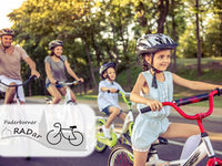 Happy family is riding bikes outdoors and smiling. Little girl in the foreground
